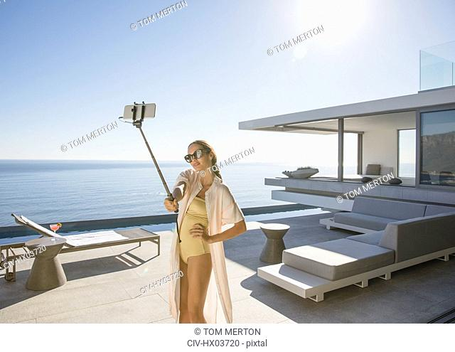 Woman in bathing suit taking selfie with selfie stick on sunny modern, luxury home showcase exterior patio with ocean view
