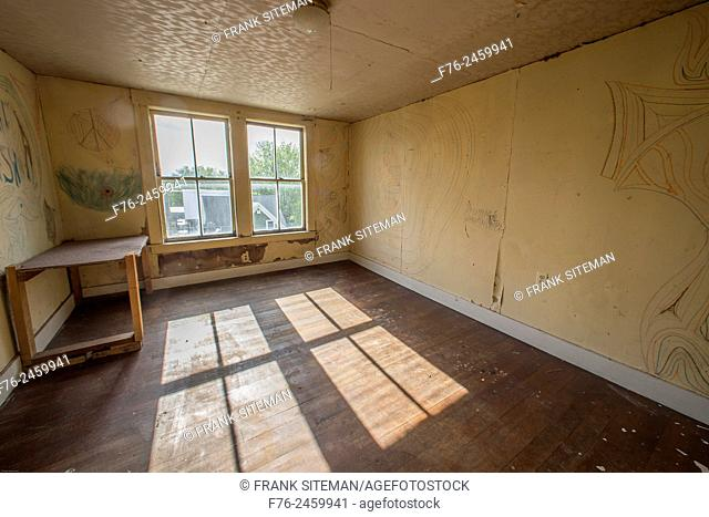 Large empty room in an abandoned house, with graffiti like drawings on the walls