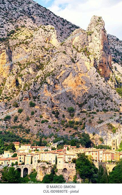 Buildings below mountain, Moustiers-Sainte-Marie, Provence-Alpes-Cote d'Azur, France, Europe