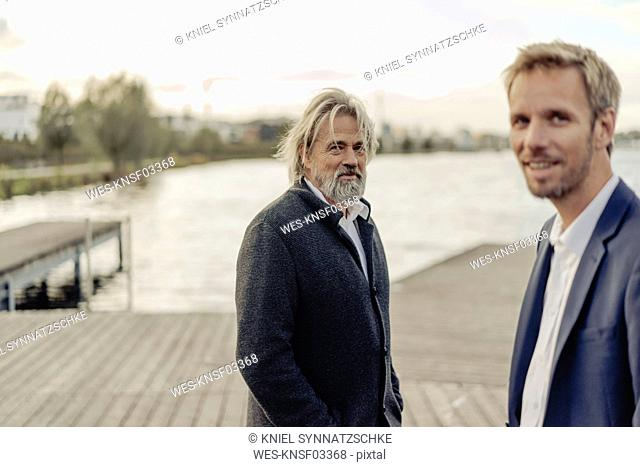 Portrait of smiling senior man and mid-adult man on jetty at a lake