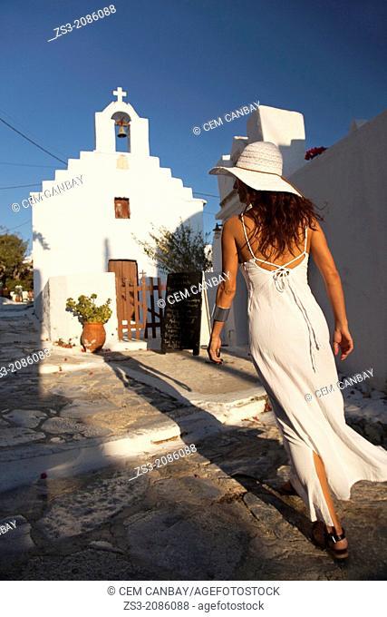 Woman walking towards a chapel, Amorgos, Cyclades Islands, Greek Islands, Greece, Europe