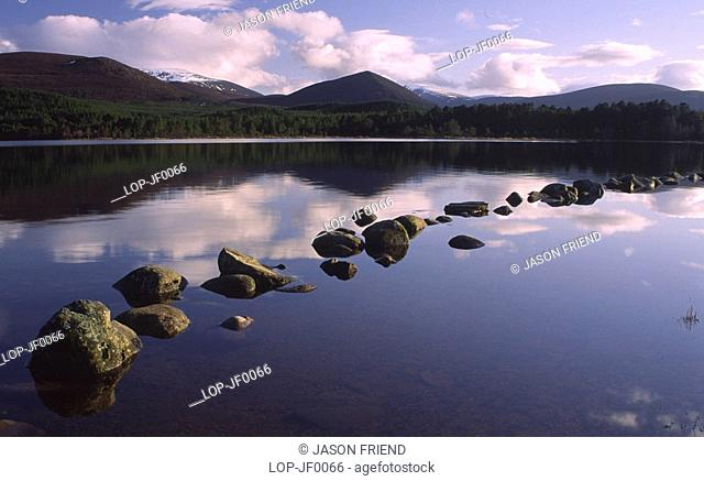 Scotland, Highland, Loch Morlich, The Cairngorm mountain range reflected in still waters of Loch Morlich