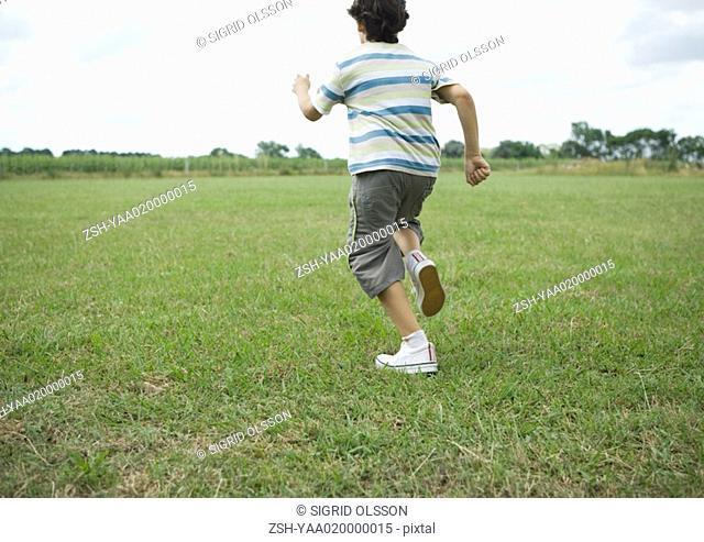 Boy running across grass, rear view