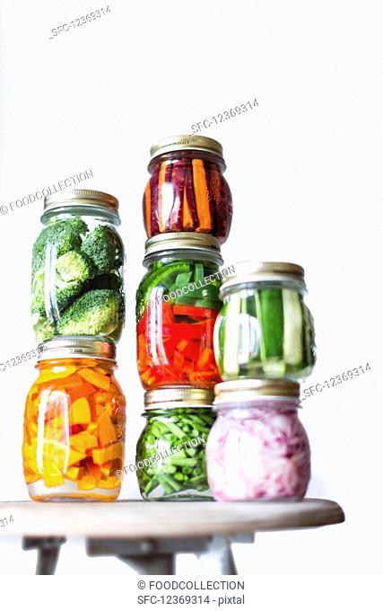 Preserving jars of freshly pickled vegetables stacked on an old stool