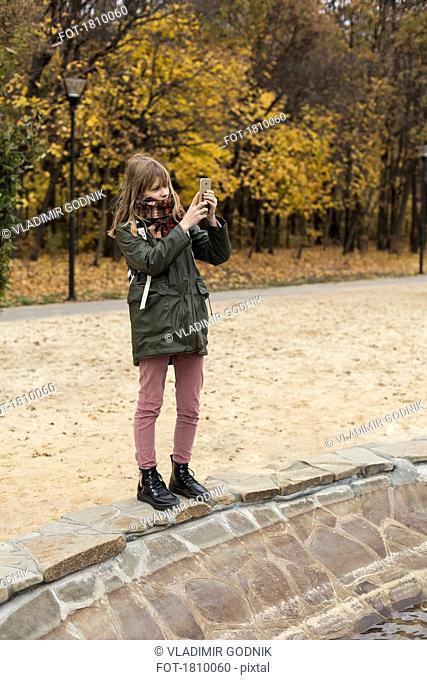 Tween girl using camera phone in autumn park