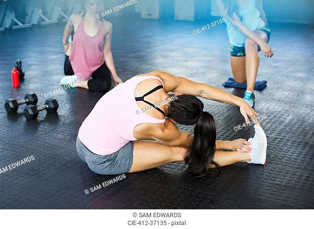 Young woman stretching leg and side in gym