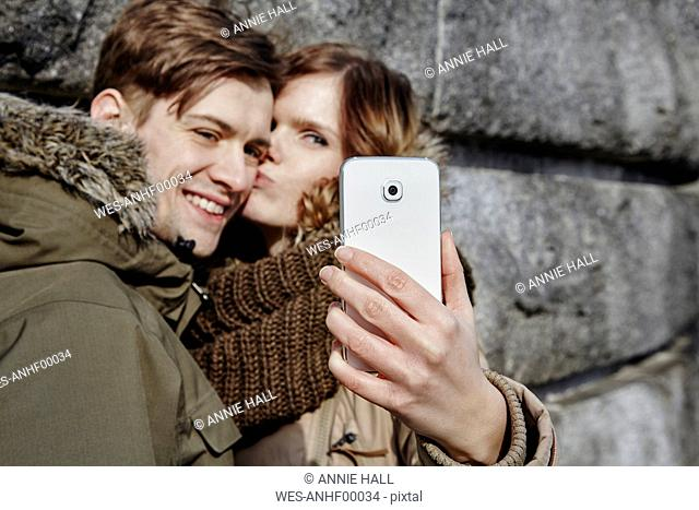 Happy young couple kissing outdoors taking a selfie