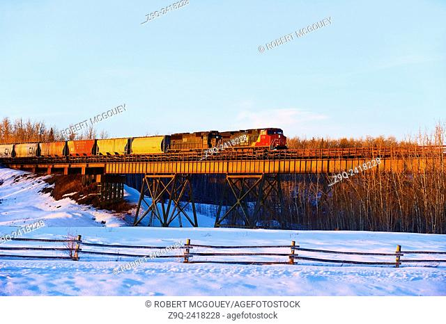 This Canadian National freight train is crossing a tressel lighted by a winters sunset in Alberta. Canada