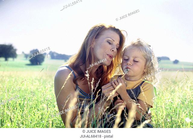 Portrait of a mother and her daughter playing in the grass