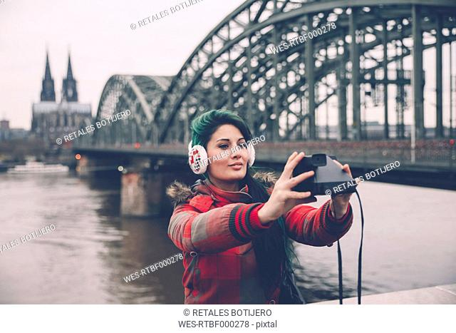 Germany, Cologne, woman taking selfie in front of Hohenzollern Bridge