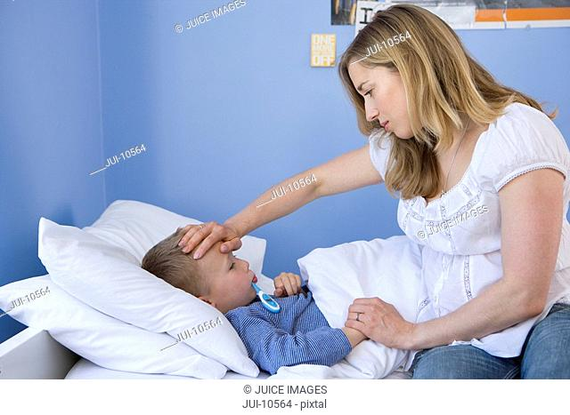 Mother taking son's 4-6 temperature, side view
