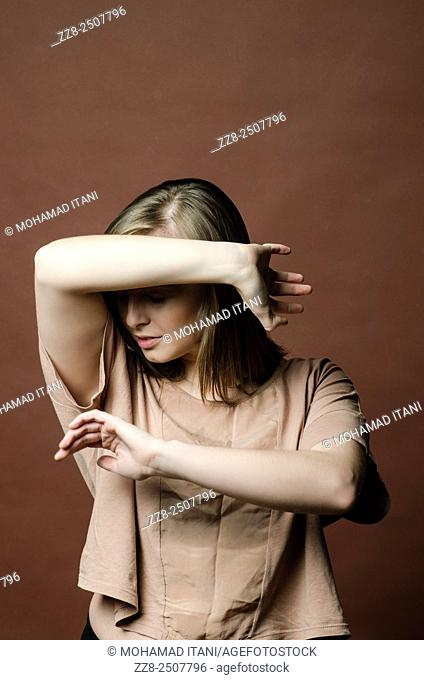Young woman in danger haiding face with hands