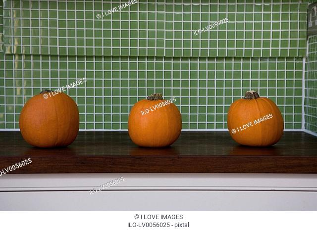 Row of orange Hallowe'en pumpkins on a kitchen counter