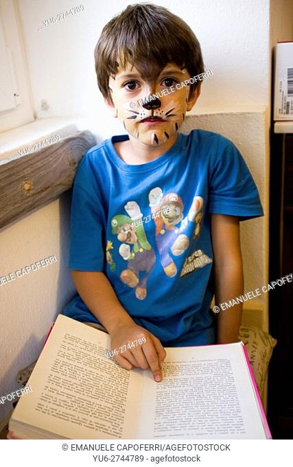 7 year old rigged as a cat reads a book near the window of the house