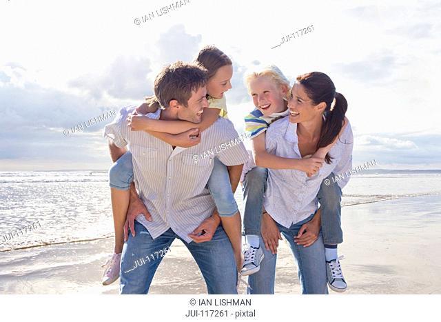 Parents Giving Children Piggybacks On Beach Vacation