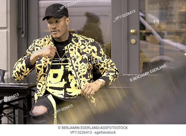 stylish man moving hands, wearing individual fashion, sitting outdoors in city, in Munich, Germany