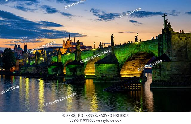 Charles bridge illuminated with green lights at sunset in Prague