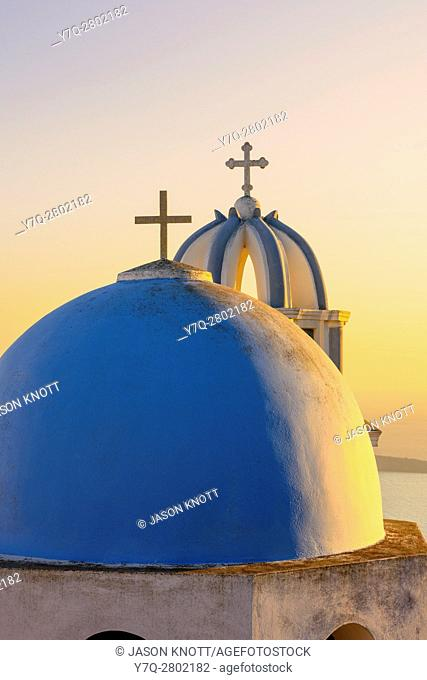 Sunset over a blue domed church on Santorini Island, Cyclades, Greece