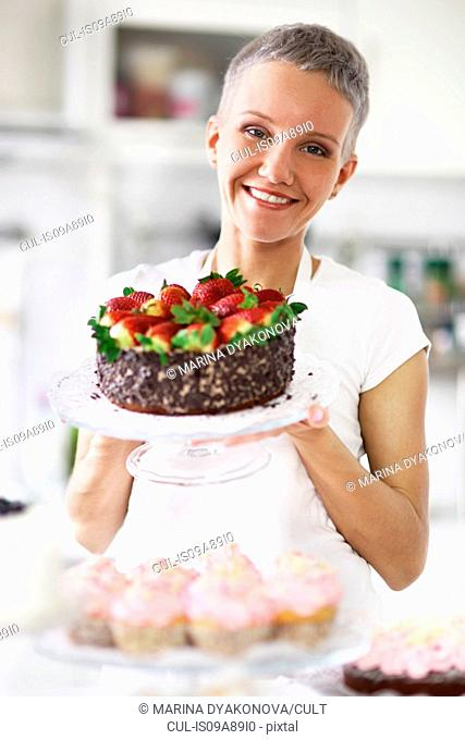 Portrait of woman holding cake with strawberries