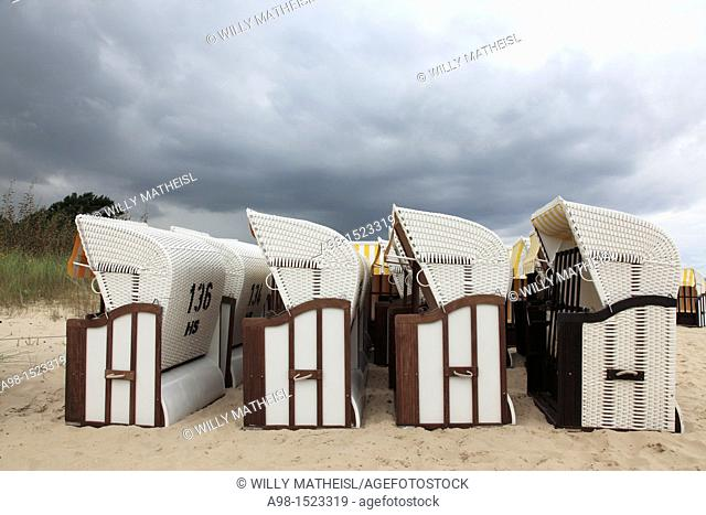 rain clouds above roofed wicker beach chair at the sandy coast of the isle of Usedom, Western Pomerania, Germany, Europe