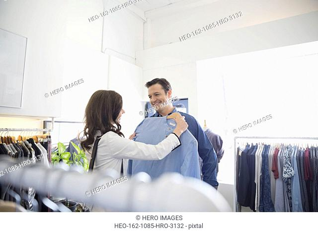 Couple looking at shirt in clothing shop