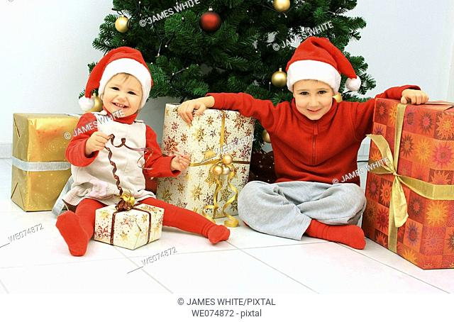 Child wearing Father Christmas hat with presents in front of Christmas Tree