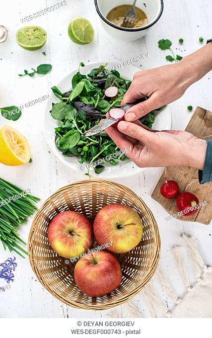 Hand preparing salad cutting red radish
