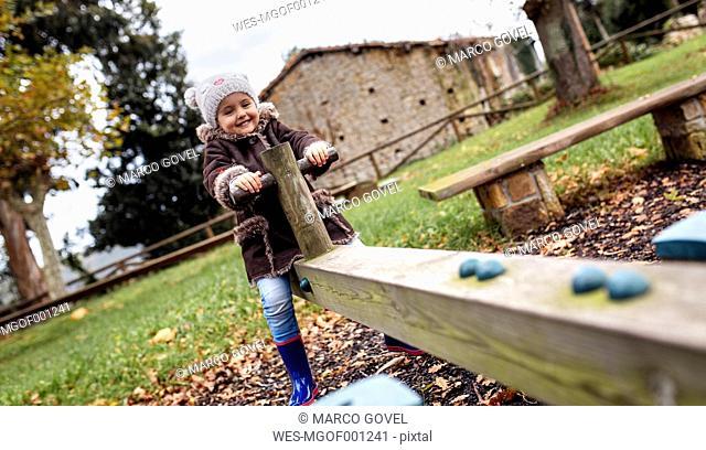 Little girl having fun on a rocker in autumn