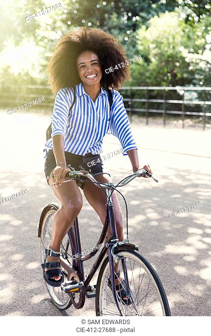 Portrait smiling woman with afro riding bicycle in park