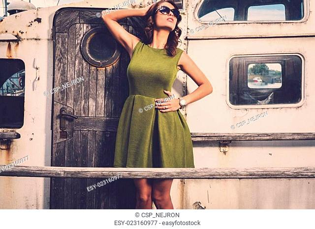 Stylish woman on old rusty boat