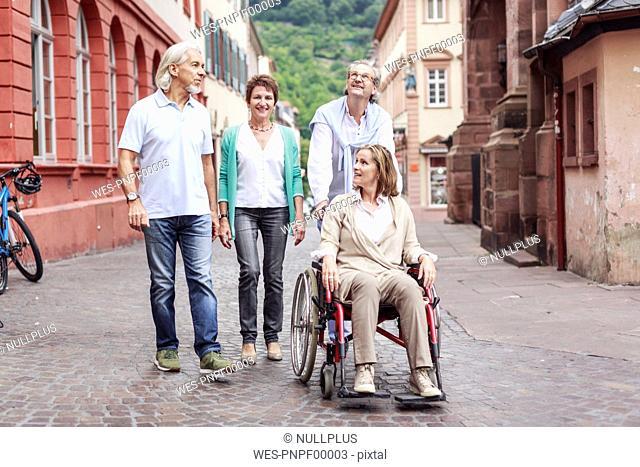 Germany, Heidelberg, senior friends with woman in wheelchair on city trip