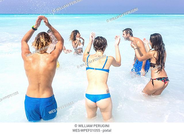 Friends having fun on the beach, jumping and splashing in the sea