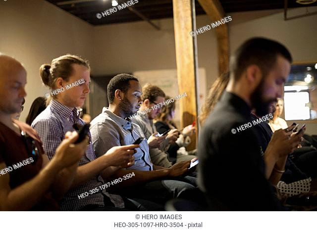 People in audience checking cell phones