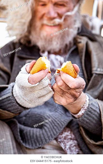 So tasty. Selective focus of bread pieces being in hands of a positive delighted man