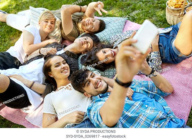 friends taking selfie on picnic at summer park