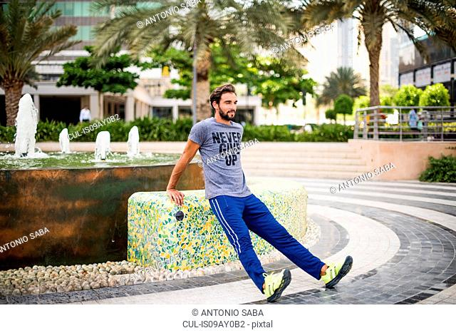 Man training, doing warm ups in park, Dubai, United Arab Emirates