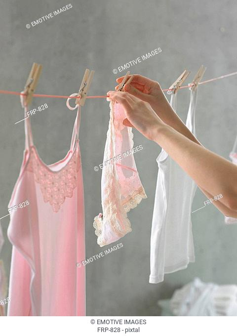 Woman is hanging a slip at a closthesline