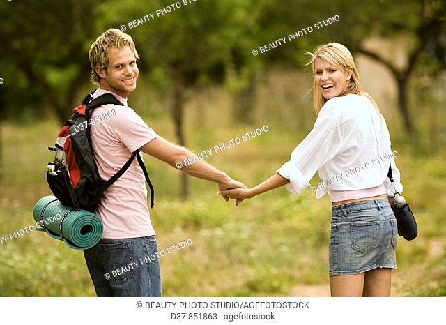 Happy couple walking hand in hand in the country