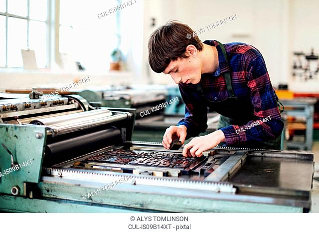 Young man working on letterpress machine in book arts workshop