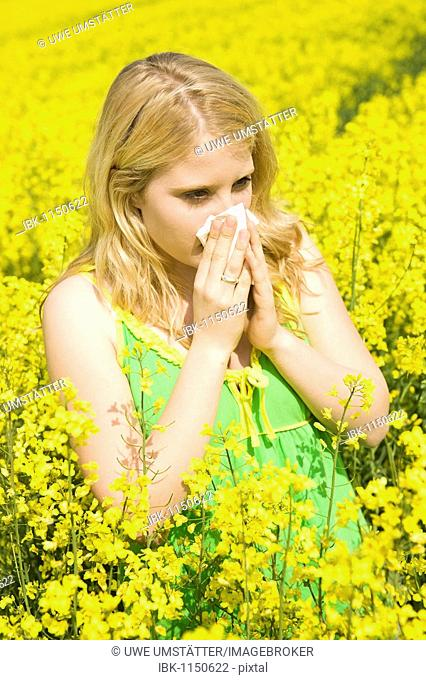 Young blond girl with an allergy standing in a field of rape