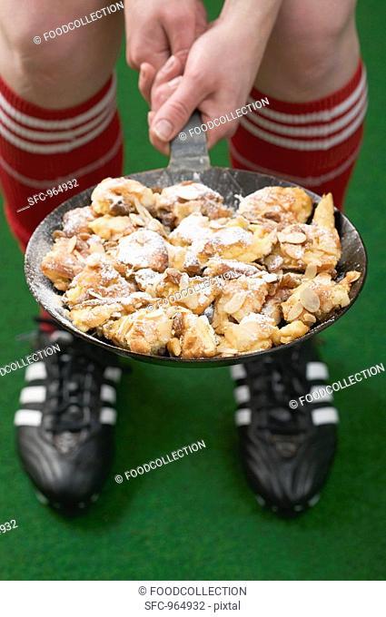 Footballer holding pan of Emperor's pancake