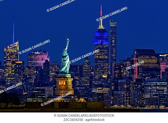 Empire State And Statue Of Liberty II - The illuminated midtown Manhattan skyline with the Empire State Building (ESB) lit up