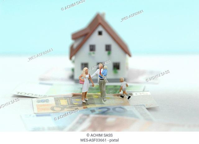 Pastic figurines on banknotes, house in background