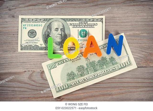 Bank notes and loan alphabet on old wooden desk. Focus on alphabet blocks