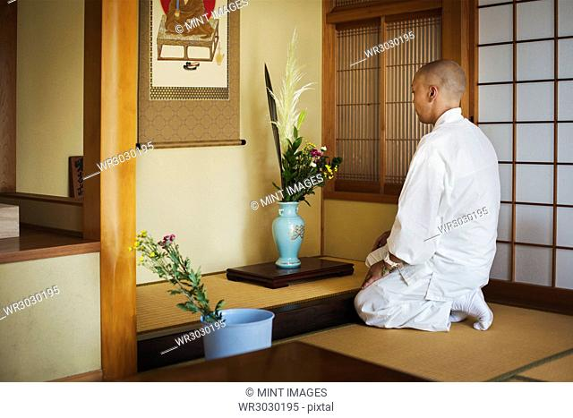 Side view of Buddhist monk with shaved head wearing white robe kneeling in front of vase with flowers