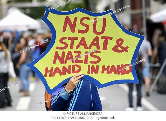 """11 July 2018, Munich, Germany: Demonstrators hold a sign saying """"""""NSU State & Nazis hand in hand"""""""" at a rally in front of the Higher Regional Court"""