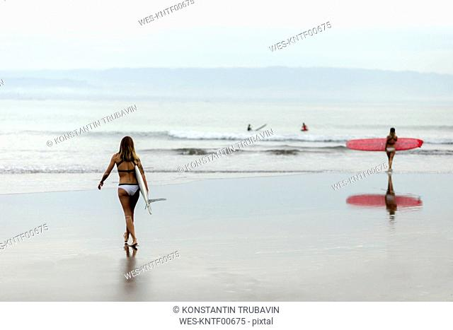Woman carrying surfboard at the sea