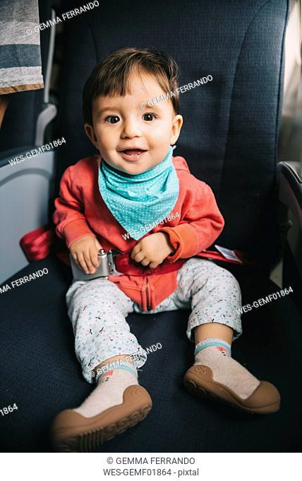 Baby sitting on a plane next to the window with a seat belt fasten