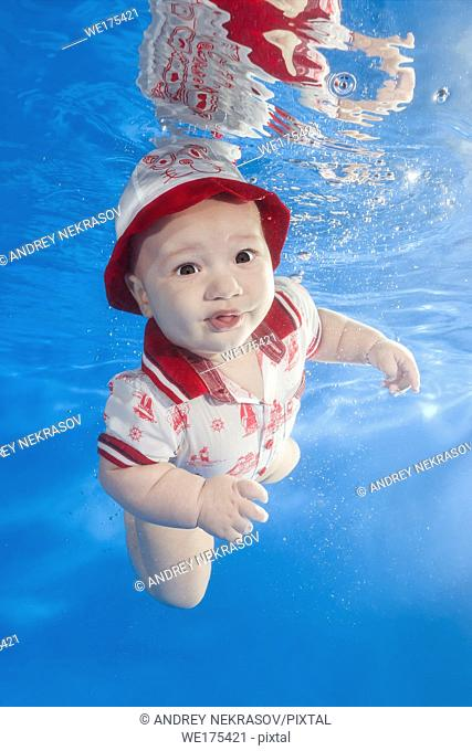 A little boy in a red cap is swimming in the pool