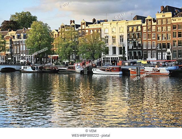 Netherlands, Amsterdam, View of houses and boat with amstel canal